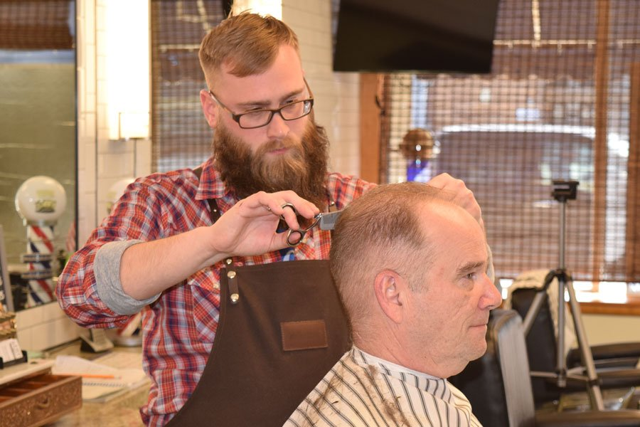 friendly barber chats with his clients while giving a haircut