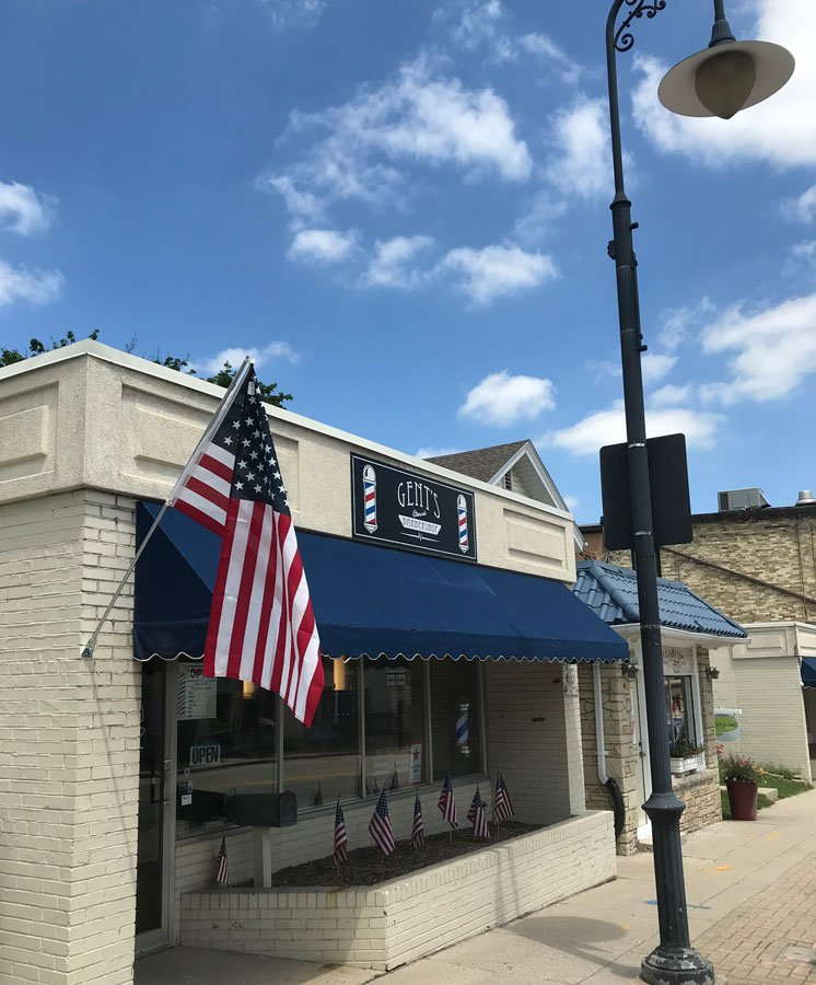 gents barbershop store front on a sunny day in menomonee falls american flag