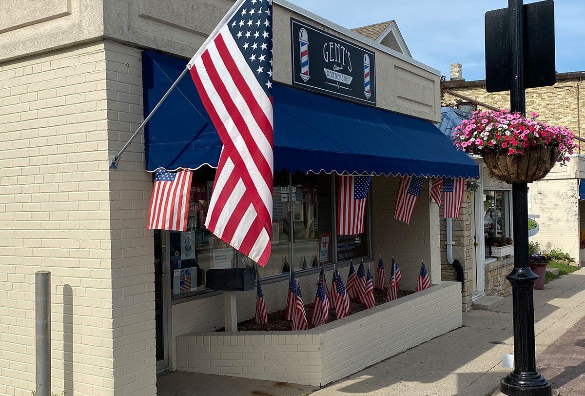 store front of gents classic barbershop on main street in menomonee falls with american flags
