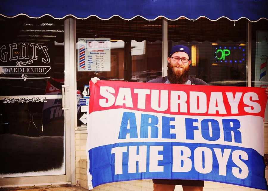 will from gents barbershop holding a saturdays are for the boys flag in front of his store on appleton and main street